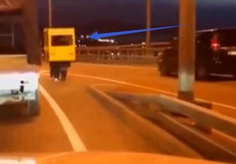 为过桥伪装成公交:4个年轻人扛着黄色车辆纸壳在俄罗斯金角湾大桥上行走
